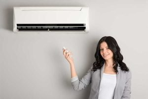 Split system reverse cycle air conditioner with lady holding remote